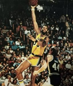 Kareem Abdul-Jabbar, who won five NBA titles withe LA Lakers during the 1980s, hoists his patented skyhook off Denver Nuggets' Dan Issel.