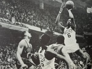 Bill Russell was known for his defensive prowess but, here in photo, he looks to score against the Philadelphia Sixers even as Wilt Chamberlain is a hapless bystander (at far left).