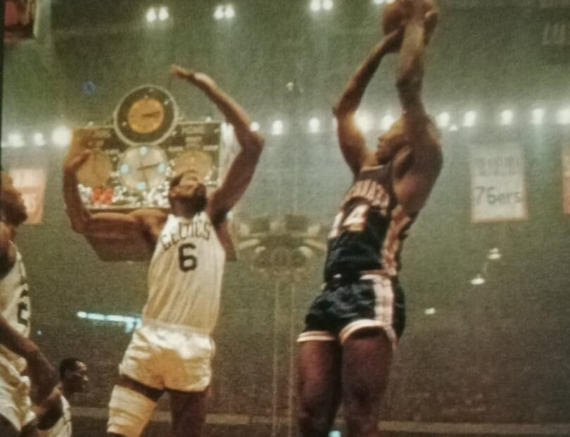 Celtics great Bill Russell hoists a hook shot over the outstretched arm of an LA Lakers defender.